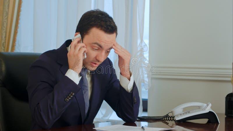 Le jeune homme d'affaires sérieux prennent un appel téléphonique, ayant une conversation et devenant songeur image libre de droits