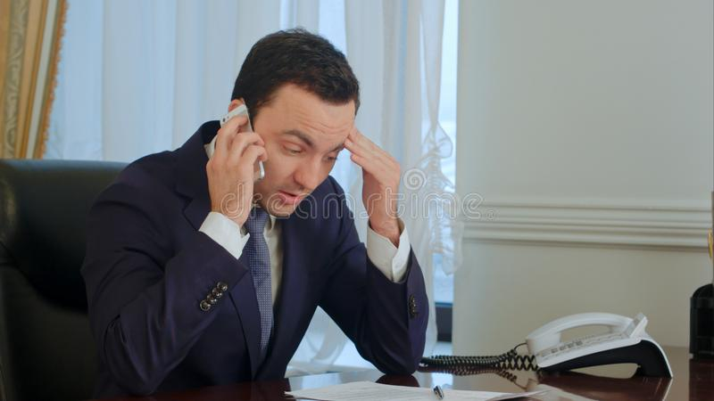 Le jeune homme d'affaires sérieux prennent un appel téléphonique, ayant une conversation et devenant songeur photographie stock libre de droits