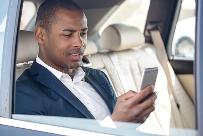 Le jeune homme d'affaires s'asseyant dans la fenêtre de voiture a ouvert vérifier des médias sociaux sur le sourire de smartphone photographie stock