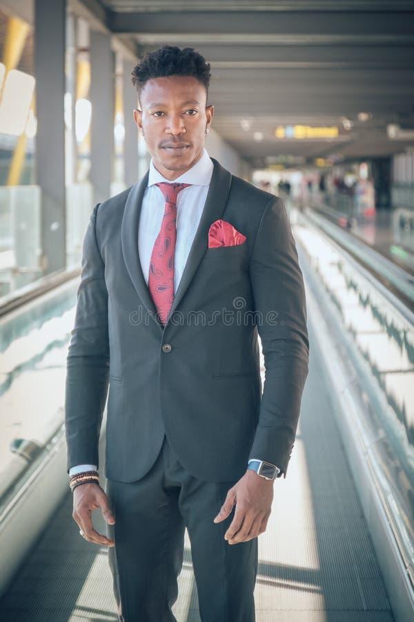 Le jeune homme d'affaires se lève en dehors de l'aéroport regardant le Th image libre de droits