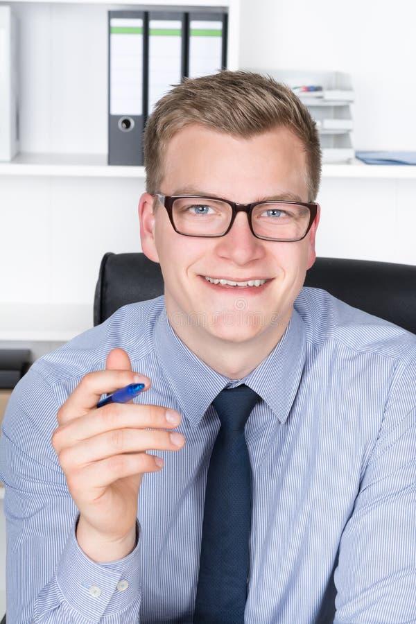 Le jeune homme d'affaires tient un stylo dans sa main photo libre de droits