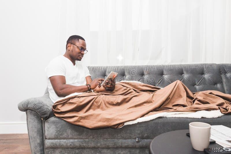 Le jeune homme d'Afro-américain, couvert de couverture, utilise le comprimé image libre de droits