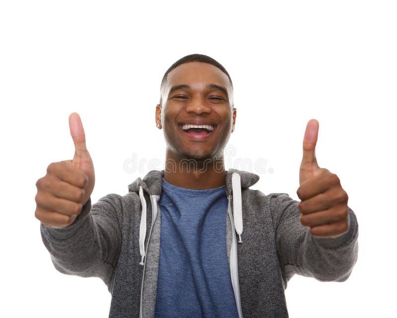 Le jeune homme d'afro-américain souriant avec des pouces lèvent le signe photo stock