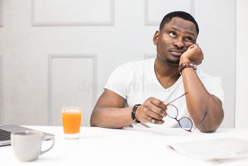 Le jeune homme d'Afro-américain tombe endormi au petit déjeuner dans la cuisine images stock