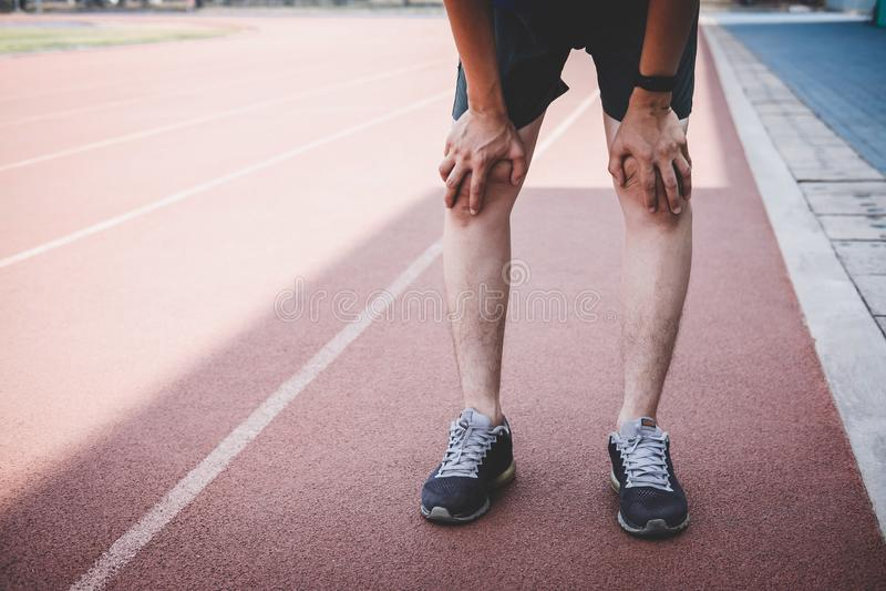 Le jeune homme d'athlète de forme physique ont un repos pendant et fatigué sur la voie de route, concept de bien-être de séance d photo libre de droits