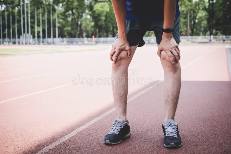 Le jeune homme d'athlète de forme physique ont un repos pendant et fatigué sur la voie de route, concept de bien-être de séance d photographie stock libre de droits