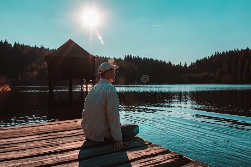 Le jeune homme dans le chapeau blanc s'asseyent sur le petit quai en bois sur l'étang avec le bâtiment en bois et le ciel bleu photo stock