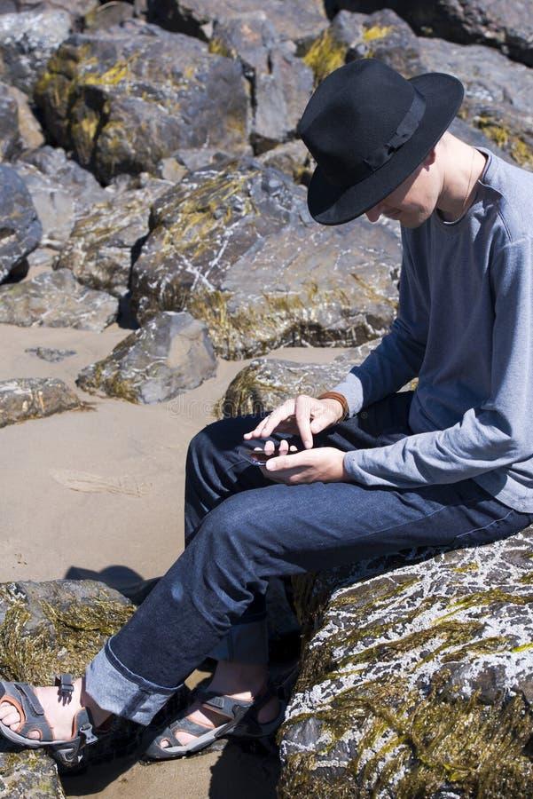 Le jeune homme dans le chapeau noir vérifie des messages dans les réseaux sociaux sur le rivage d'océan photographie stock libre de droits