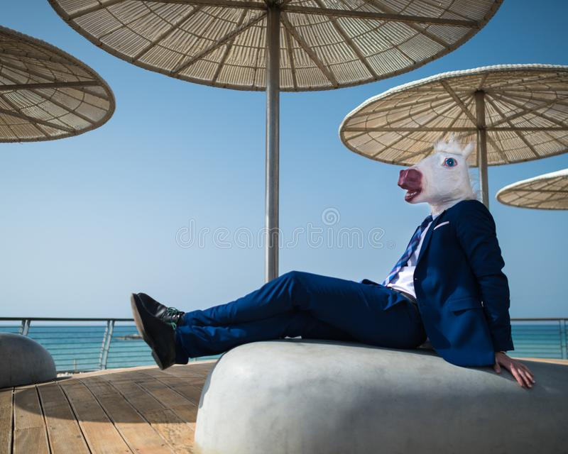 Le jeune homme dans le costume élégant s'assied sous des parapluies sur le bord de mer de ville photo stock