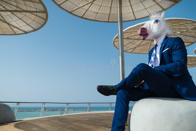 Le jeune homme dans le costume élégant s'assied sous les parapluies élégants sur le bord de mer de ville images stock