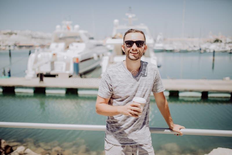 Le jeune homme dans des lunettes de soleil boivent du café pour aller sur la rue d'été avec le port de yacht sur le fond concept  photos stock