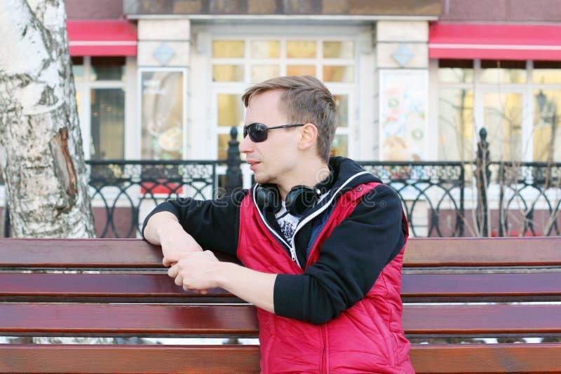 Le jeune homme dans des lunettes de soleil et avec des écouteurs s'assied sur le banc image stock
