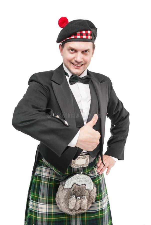 Le jeune homme dans l'habillement pour l'écossais dansent montrant des pouces  image libre de droits