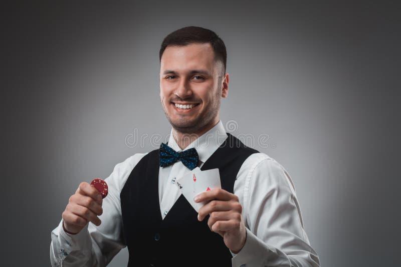 Le jeune homme dans la chemise et le gilet montre ses cartes et tient des jetons de poker dans des ses mains, tir de studio photos stock