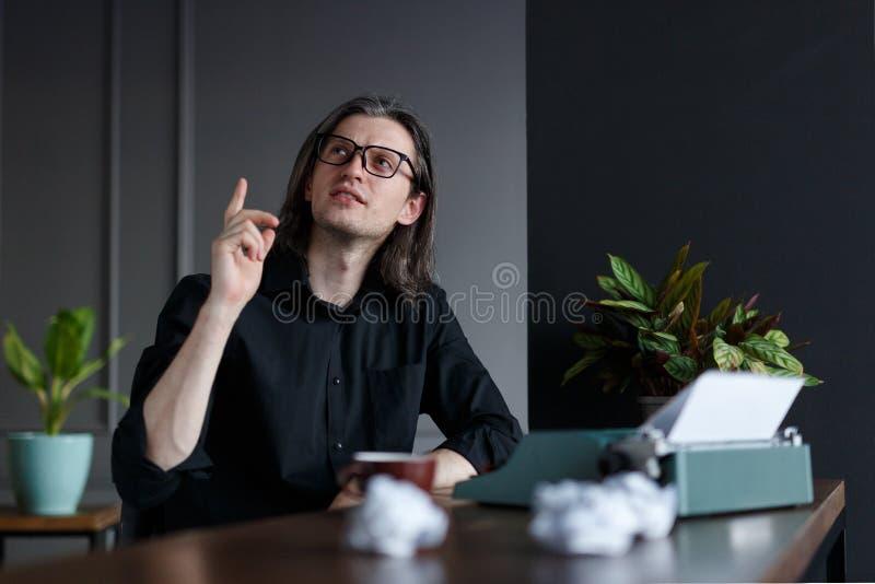 Le jeune homme dans la chemise noire, avec de longs cheveux, augmentés son doigt vers le haut d'exposition ont un ideea, posé à u image stock