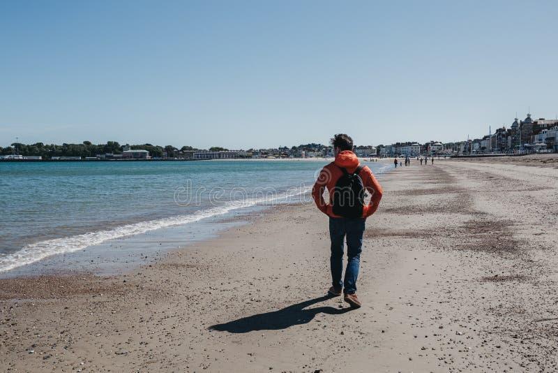 Le jeune homme dans la veste rouge et les jeans marchant sur Weymouth échouent, Dorset, Angleterre images libres de droits