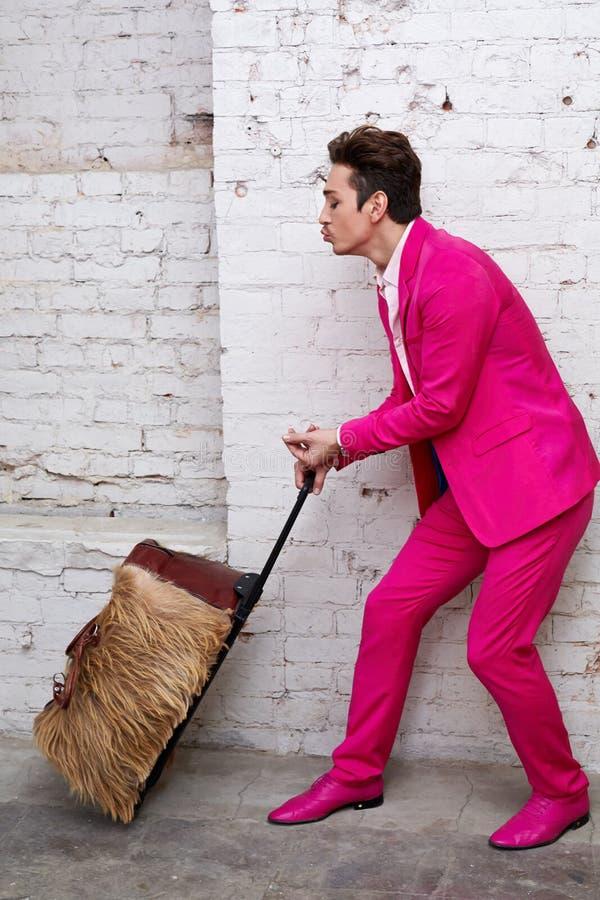 Le jeune homme dans le costume rose tire le sac de rouleau photo libre de droits