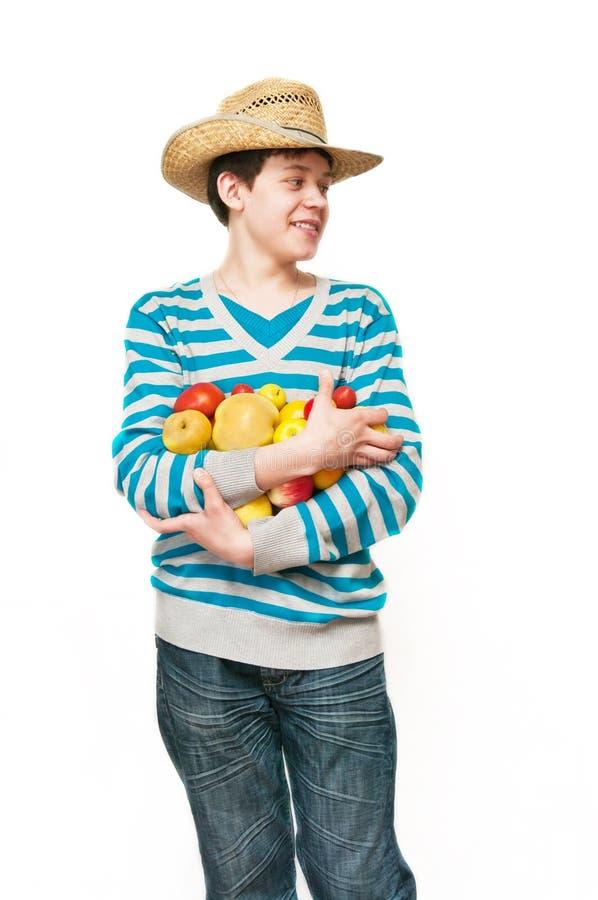 Le jeune homme dans un chapeau de paille avec le fruit photo stock