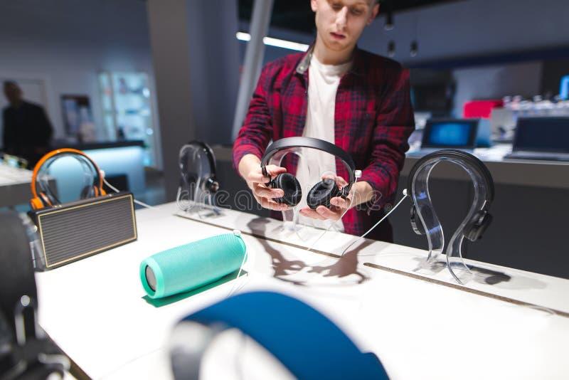 Le jeune homme dans une chemise rouge se tient dans un magasin de technologie avec des écouteurs dans des ses mains photo libre de droits