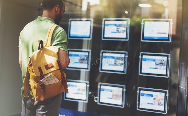Le jeune homme de hippie avec le sac à dos et la carte regardant l'hôtel d'affiche de promo d'annonce, choisissent des appartemen photos stock