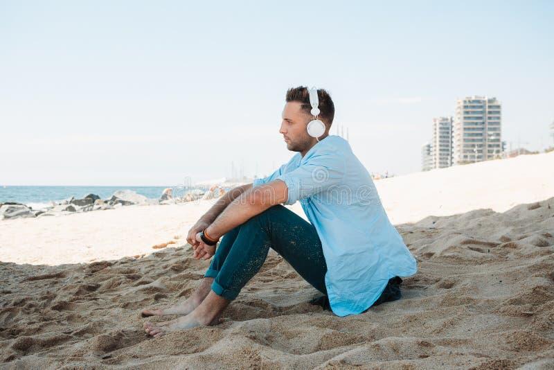 Le jeune homme de hippie dans une chemise bleue et des jeans écoutant la musique dans des écouteurs sur un smartphone et s'assied images stock