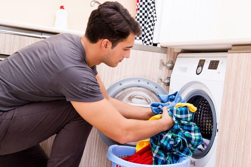 Le jeune homme de mari faisant la blanchisserie à la maison photos libres de droits