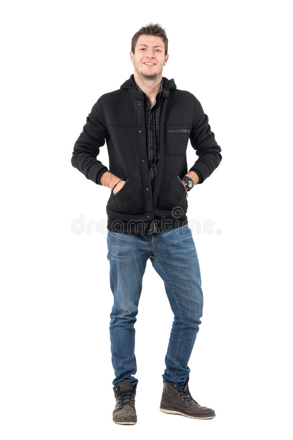Le jeune homme de sourire décontracté heureux avec des mains dans la veste à capuchon empoche regarder l'appareil-photo photos libres de droits