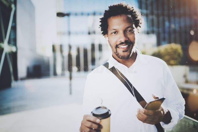 Le jeune homme de sourire d'Afro-américain dans l'écouteur marchant à la ville ensoleillée avec emportent le café et apprécier po photographie stock libre de droits