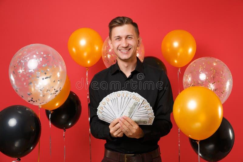 Le jeune homme de sourire dans la chemise classique noire tenant un bon nombre de paquet de dollars encaissent l'argent sur les b photos libres de droits
