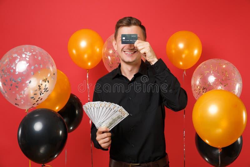Le jeune homme de sourire dans la chemise classique tenant un bon nombre de paquet de dollars encaissent l'argent couvrant des ye images stock