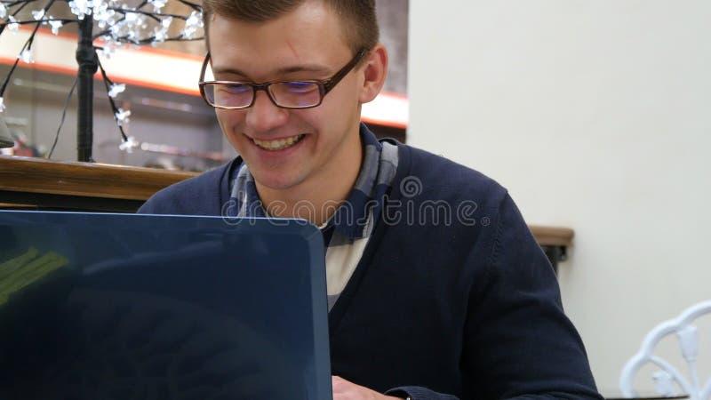 Le jeune homme de sourire en verres s'asseyent à la table dans le centre commercial et au fonctionnement sur un ordinateur portab photos stock