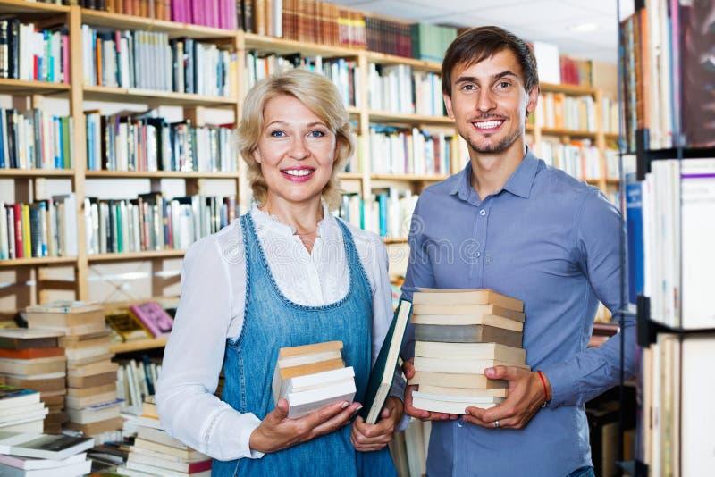 Le jeune homme de sourire et mûrissent la femme tenant des livres photo stock