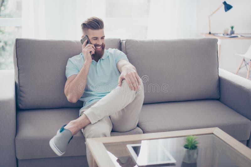 Le jeune homme de sourire parle à son téléphone, se reposer décontracté sur le Th image libre de droits