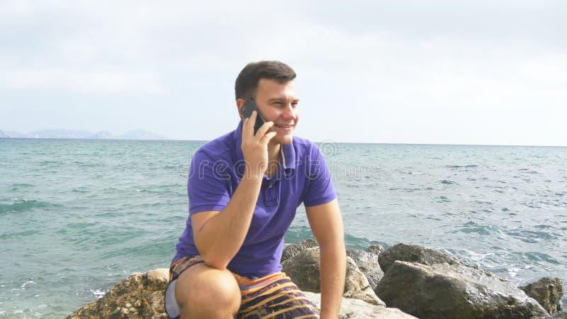 Le jeune homme de sourire parle au téléphone portable sur la plage en mer Type heureux beau s'asseyant sur la pierre près de l'oc image stock