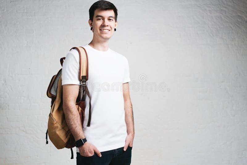 Le jeune homme de sourire utilisant le T-shirt et le sac à dos blancs vides, vident le mur images stock