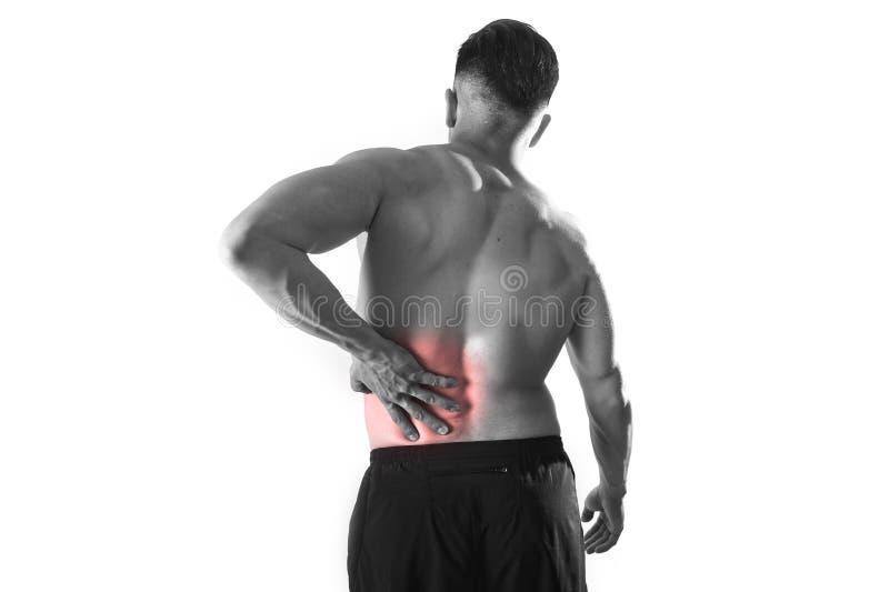 Le jeune homme de sport de corps musculaire tenant la taille lombo-sacrée endolorie souffrent la douleur dans l'effort d'athlète image stock