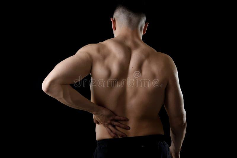 Le jeune homme de sport de corps musculaire tenant la taille lombo-sacrée endolorie souffrent la douleur dans l'effort d'athlète photos libres de droits