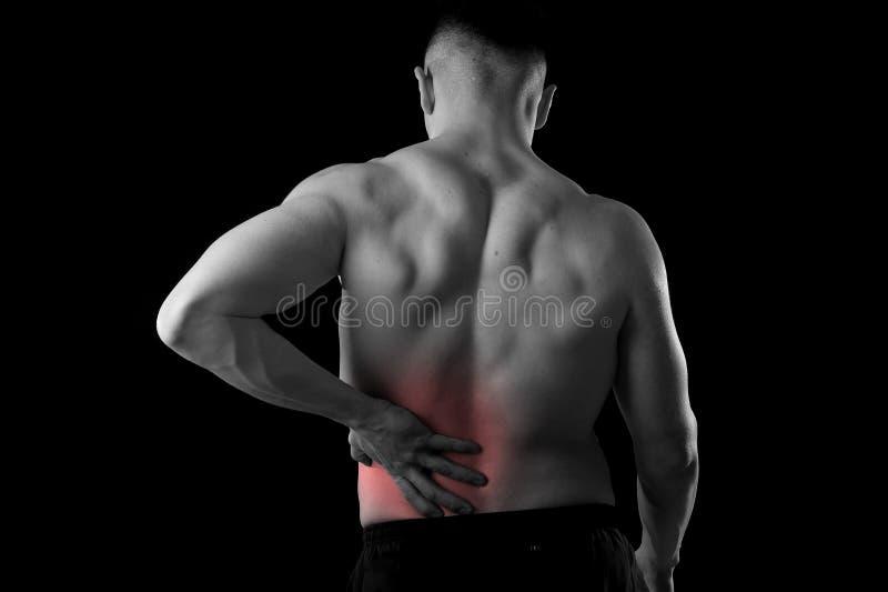 Le jeune homme de sport de corps musculaire tenant la taille lombo-sacrée endolorie souffrent la douleur dans l'effort d'athlète images libres de droits