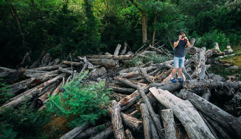 Le jeune homme de voyageur se tient sur des rondins et prend des photos sur l'appareil-photo de Smartphone avec le Copie-espace l photos stock
