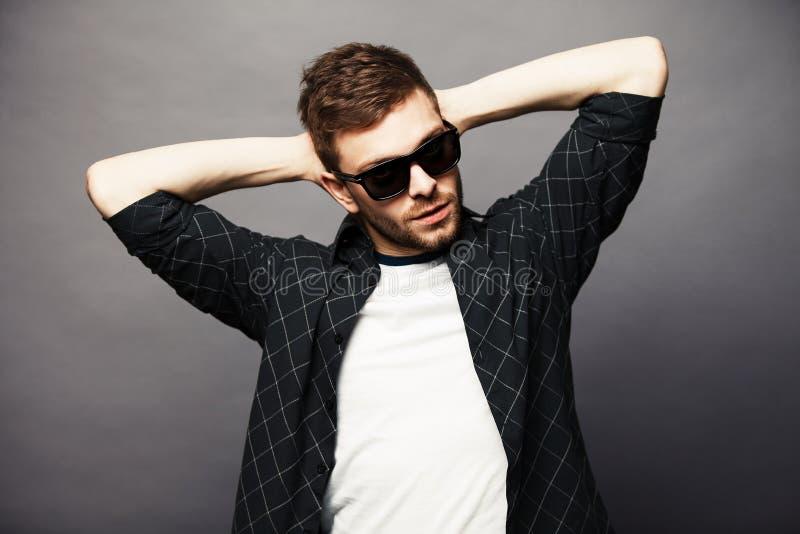 Le jeune homme dedans avec des lunettes de soleil sourit heureusement photographie stock