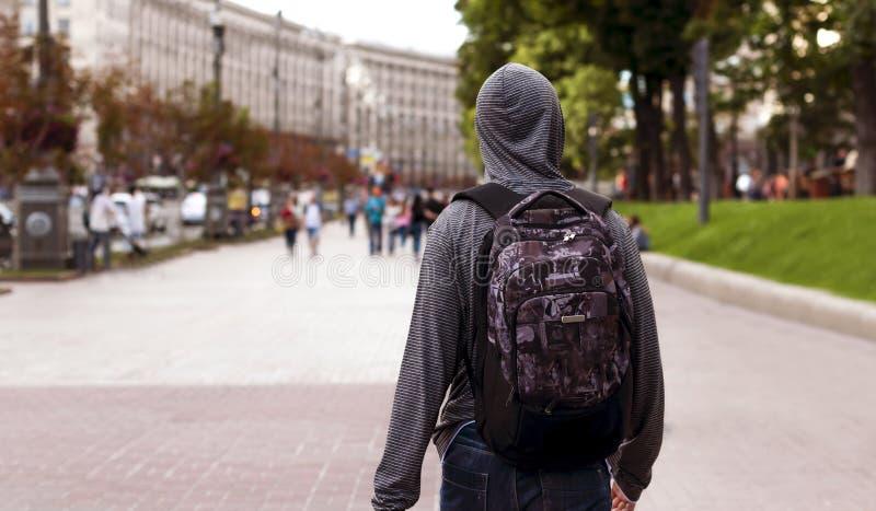 Le jeune homme descend la rue d'une grande ville photo stock