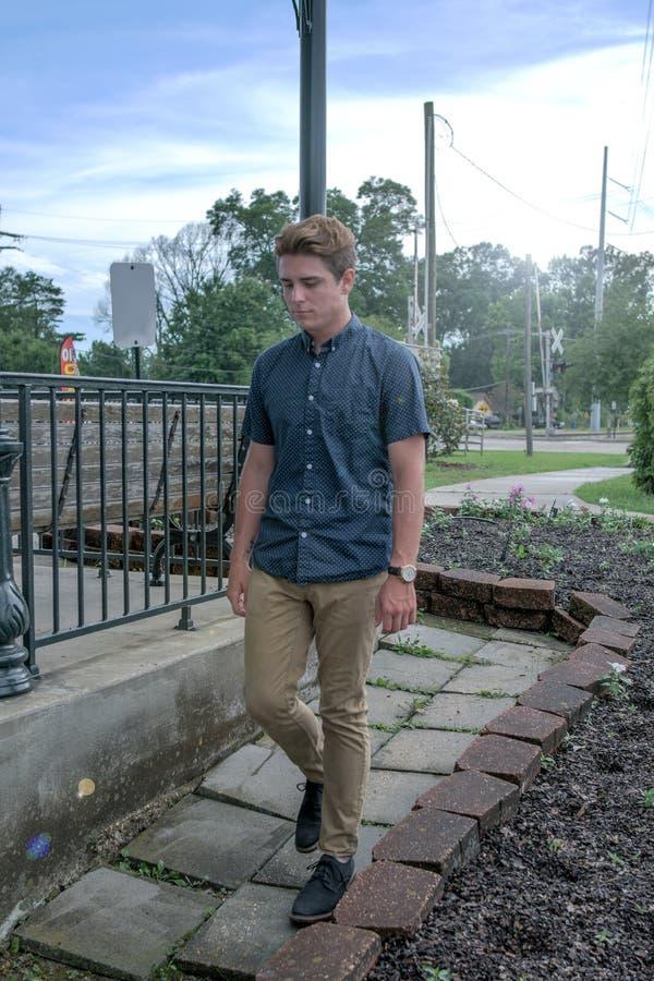 Le jeune homme descend un chemin carrelé en pierre photo stock