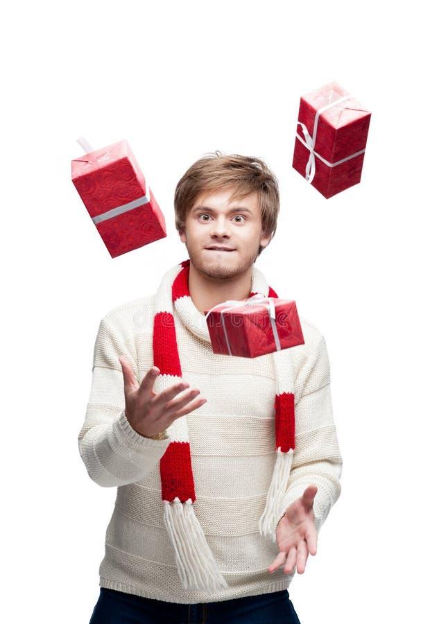 Le jeune homme drôle jonglent les cadeaux de Noël images libres de droits