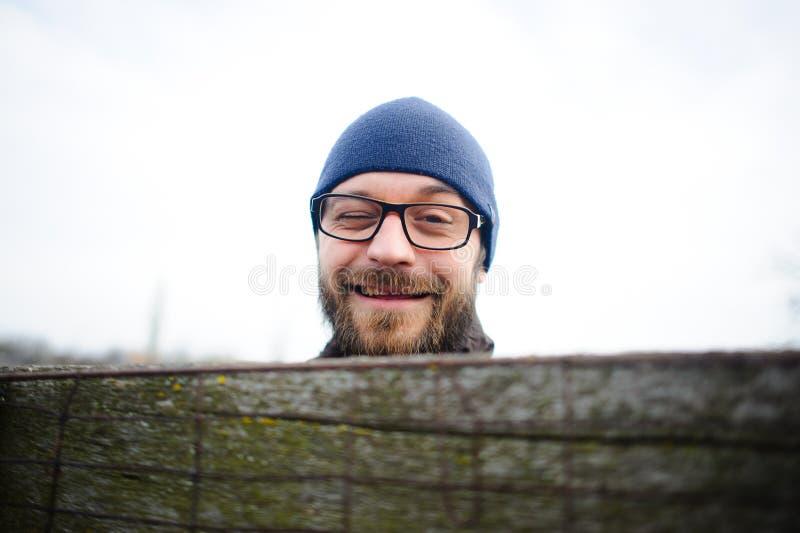 Le jeune homme drôle avec des verres et une barbe regarde par derrière la barrière Il photographie stock