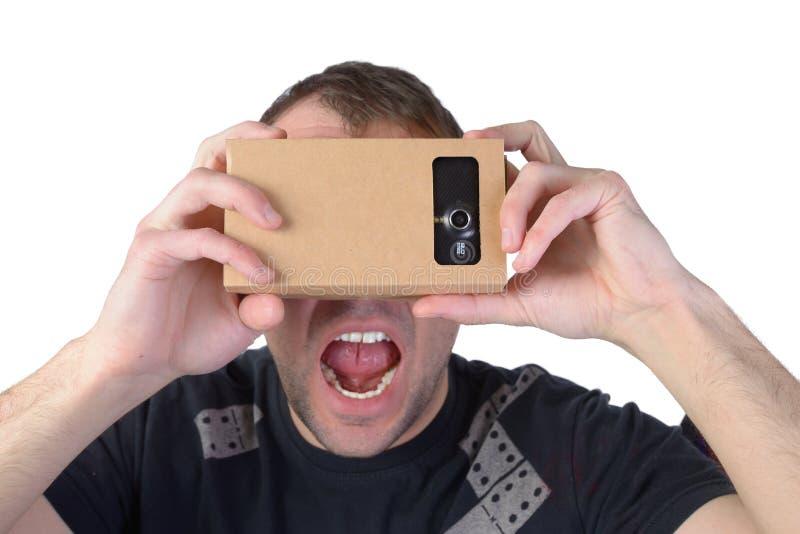 Le jeune homme emploie la réalité virtuelle (carton de VR) d'isolement sur le fond blanc photographie stock libre de droits