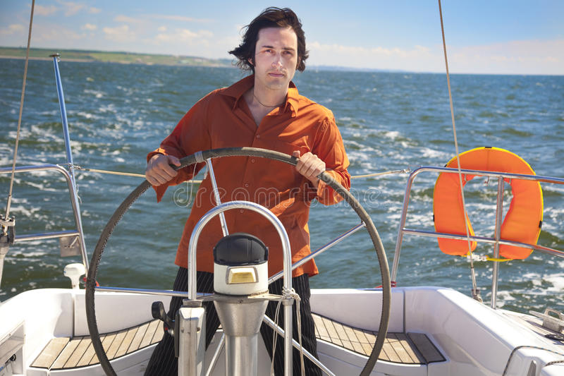 Le jeune homme est pilote de bateau à voiles images libres de droits