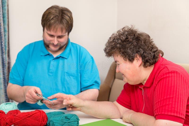Le jeune homme et la femme handicapée tricotent ensemble image stock