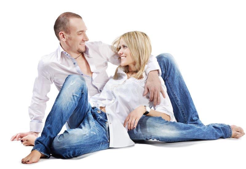 Le jeune homme et la femme s'asseyent sur l'étage photographie stock