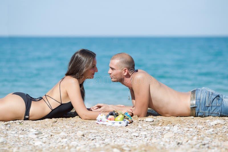 Le jeune homme et la femme se trouvent sur le sable contre la mer photographie stock libre de droits