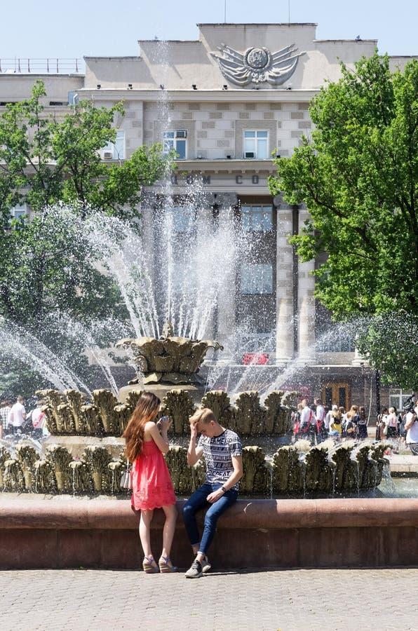 Le jeune homme et la fille en parc de ville près de la fontaine photographie stock